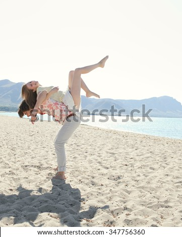 Young tourist couple on holiday, with man carrying girl on back with legs up, on beach destination with sunny blue sky, outdoors space. Romance and dynamic honeymoon fun lifestyle, summer exterior.