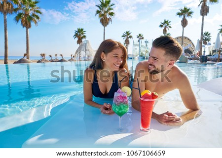 Young tourist couple on infinity pool drinking cocktails at resort on the beach #1067106659