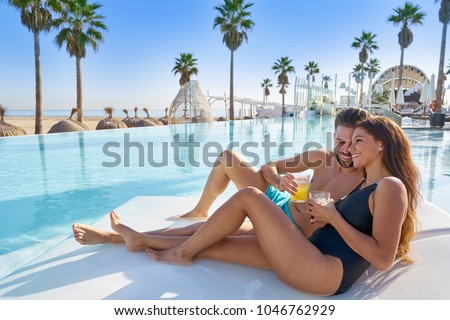 Young tourist couple on infinity pool hammock at resort on the beach drinking soda #1046762929