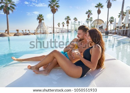 Young tourist couple on infinity pool hammock at resort on the beach drinking soda #1050551933