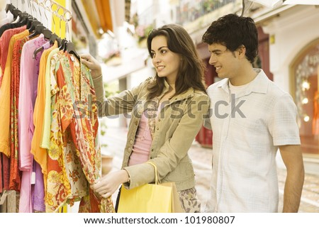 Young tourist couple shopping for souvenirs in a vacations destination.