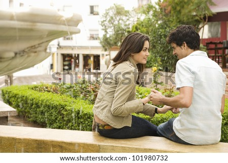 Young tourist couple sitting by fountain, holding hands and smiling.