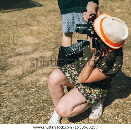 Young tourist female woman using her dslr camera taking pictures photograph in the field in sunny day photographing wearing hat and dress