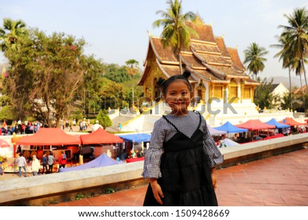 Young tourist girl is enjoying a visit at famous touristic sight in Luang Prabang, Laos