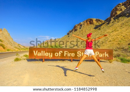 Young tourist girl jumping at welcome sign entrance of Valley of Fire State Park. Summer travel holidays in Nevada, United States. Valley of Fire is located in the Mojave Desert 58 miles of Las Vegas.