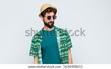 young tourist man feeling sad, upset or angry and looking to the side with a negative attitude, frowning in disagreement against white wall