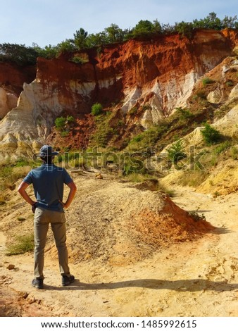 young tourist man in middle of orange ochre hills called French Colorado near Rustrel village in Luberon Valley, Provence region, southern France, Europe, popular touristic attraction in Provence #1485992615