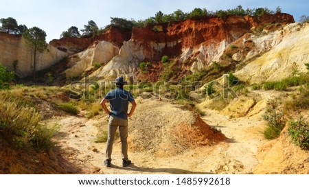 young tourist man in middle of orange ochre hills called French Colorado near Rustrel village in Luberon Valley, Provence region, southern France, Europe, popular touristic attraction in Provence #1485992618