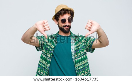 young tourist man looking sad, disappointed or angry, showing thumbs down in disagreement, feeling frustrated against white wall
