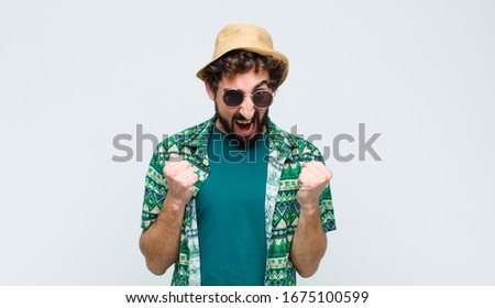 young tourist man shouting aggressively with annoyed, frustrated, angry look and tight fists, feeling furious against white wall