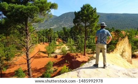 young tourist man standing in orange ochre hills called French Colorado near Rustrel village in Luberon Valley, Provence region, southern France, Europe, popular touristic attraction in Provence #1485992978