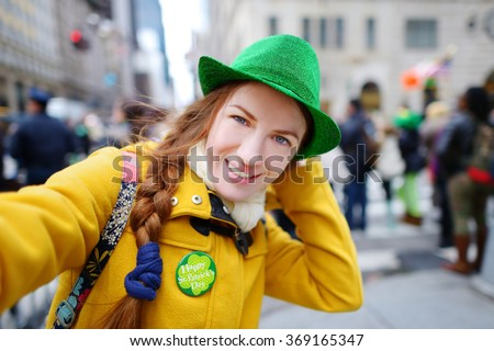Young tourist taking a selfie with her smartphone during the annual St. Patrick\'s Day Parade on 5th Avenue in New York City