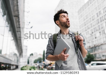 Young tourist traveler with backpack and laptop computer walks on the street, very surprised eyes wide open, emotional face. Portrait of stylish bearded man holding modern device.   #1129580393