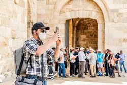 Young tourist wearing a protective mask, taking pictures with his mobile phone in Jerusalem, at the entrance to the old city.