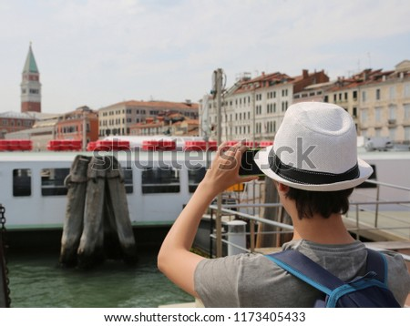 young tourist while photographing the bell tower of san marco in Venice from the boat #1173405433