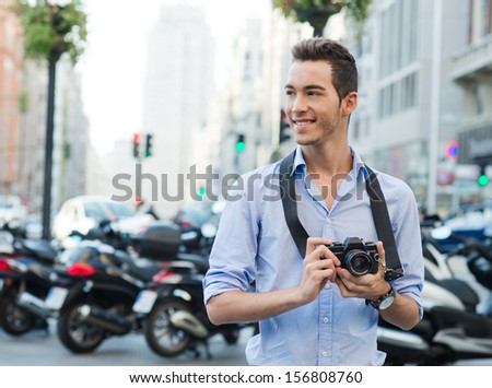 YOung tourist with a camera looking to take a pic