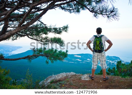 young tourist with backpack sitting on a hill and looks down