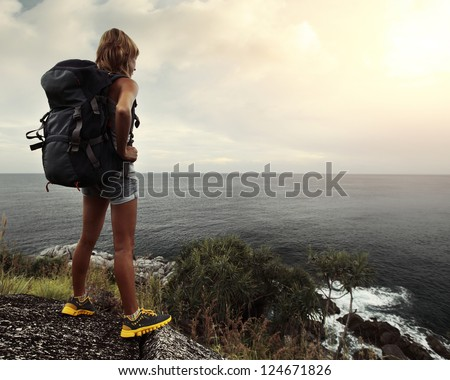 Young tourist with backpack standing on top of a hill and looking to a sea