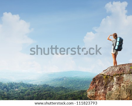 Young tourist with backpack standing on top of a mountain and enjoying morning valley view