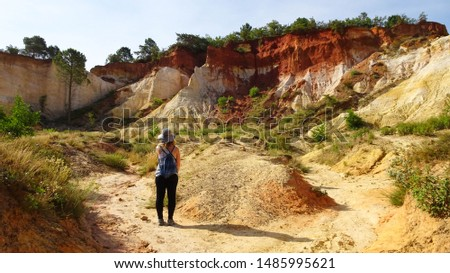 young tourist woman in middle of orange ochre hills called French Colorado near Rustrel village in Luberon Valley, Provence region, southern France, Europe, popular touristic attraction in Provence #1485995621