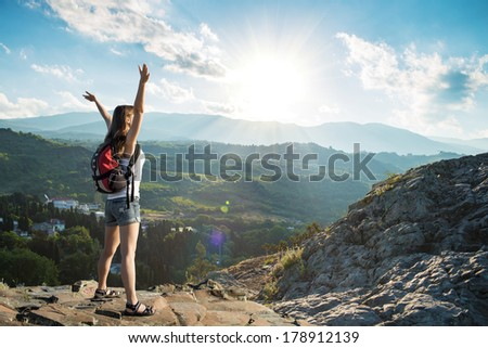 Young tourist woman is feeling free and standing with hands up  on the top of the mounting and looking at a beautiful landscape #178912139