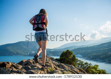 Young tourist woman is hiking on the top of the mounting and looking at a beautiful sea landscape