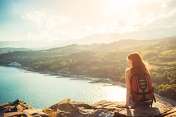 Young tourist woman is sitting on the top of the mounting and looking at a beautiful sea bay landscape. Hiking woman with backpack relaxing on the top of the cliff enjoying sunlit sea view.