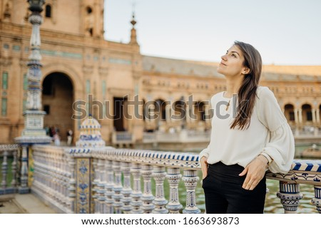 Young tourist woman looking over Plaza de Espana  in, Seville (Sevilla), Andalusia, Spain.Traveling to Spain.Sunset on Spain Square.Female  traveler visiting Spain,enjoying view,mindful walk.