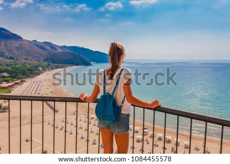 Young tourist woman on the beach and sea landscape with Sperlonga, Lazio, Italy. Scenic resort town village with nice sand beach and clear blue water. Famous tourist destination in Riviera de Ulisse #1084455578