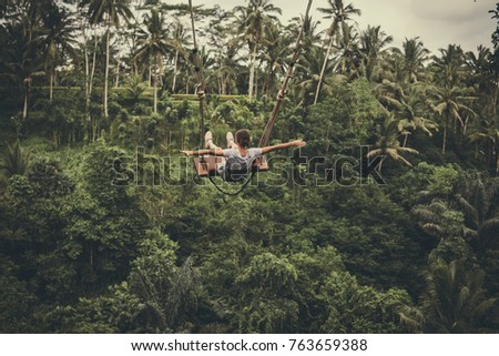 Young tourist woman swinging on the cliff in the jungle rainforest of a tropical Bali island. #763659388
