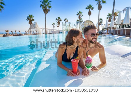 Young tourists couple on infinity pool drinking cocktails at resort on the beach #1050551930