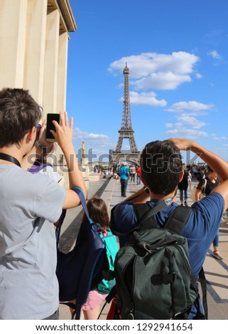 young tourists photograph the Eiffel Tower in Paris seen from the Trocadero #1292941654