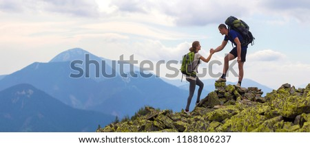 Young tourists with backpacks, athletic boy helps slim girl to clime rocky mountain top against bright summer sky and mountain range background. Tourism, traveling and healthy lifestyle concept. #1188106237