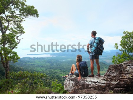 Young tourists with backpacks enjoying valley view from top of a mountain - stock photo