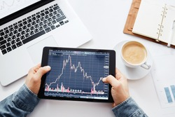 Young trader is sitting in home at table, working on tablet with graphs,diagrams on monitor. Crypto currencies, trader using tablet and computers.