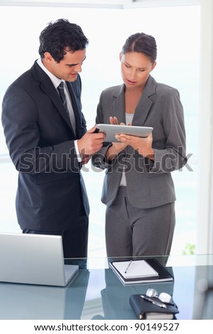 Young tradesman explaining functionality of tablet to his colleague