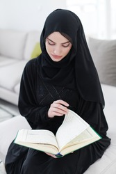 young traditional muslim woman reading Quran on the sofa before iftar dinner during a ramadan feast at home