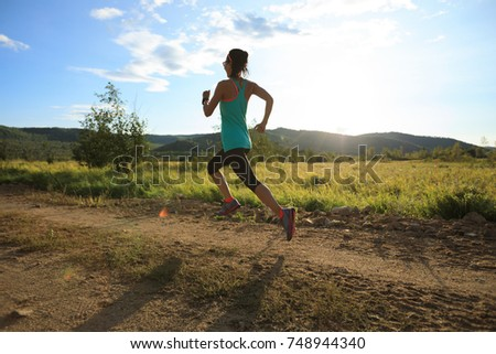 young trail runner woman running on sunset forest #748944340