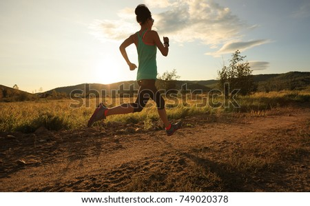 young trail runner woman running on sunset forest #749020378