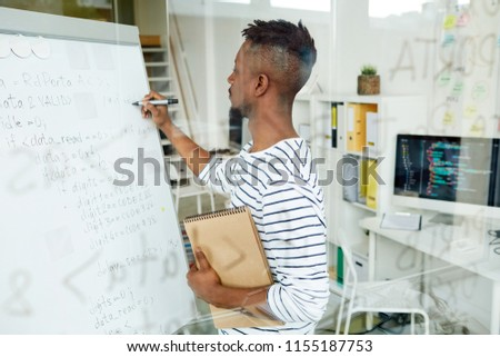 Young trainee with notepad writing down software codes on whiteboard in office
