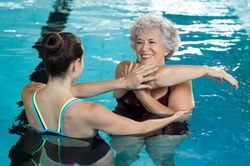 Young trainer helping senior woman in aqua aerobics. Senior retired woman staying fit by aqua aerobics in swimming pool. Happy old woman stretching in swimming pool with young trainer.