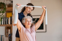 Young trainer helping senior woman with resistance band. Lovely physiotherapy health worker exercise with old woman at home. Happy smiling senior woman using rubber band to improve her muscle tone.