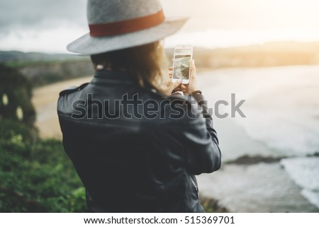 Young traveler girl shooting video of beautiful sunrise on the ocean via smartphone device, woman in hipster style taking a photo with cellphone camera an amazing ocean, travel lifestyle