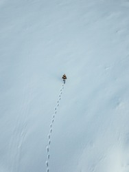 Young traveler girl walking in the deep snow,captured from above with drone