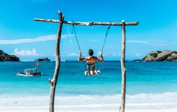 Young traveler guy is standing on swing on the beautiful beach in Bali. He is enjoying the Gloomy sand beach with the turquoise sea  background at the paradise of indonesia.  backpacker make a trip .