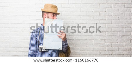 Young traveler man wearing backpack and a vintage camera covering mouth, symbol of silence and repression, trying not to say anything. Holding a map.
