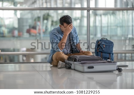 Young traveler man with casual clothes sitting on the floor at the terminal airport, unpack luggage ,problem passport lost during his vacation, Unhappy ,trouble traveling concept.