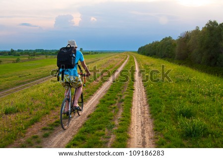 Young traveler riding bicycle on country road.