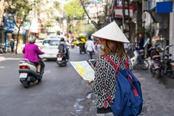 Young traveler with backpack reading a map at old quarter in Hanoi, Vietnam