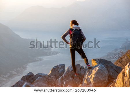 Young traveler with backpack standing on the big stones on the mountain and observing locality